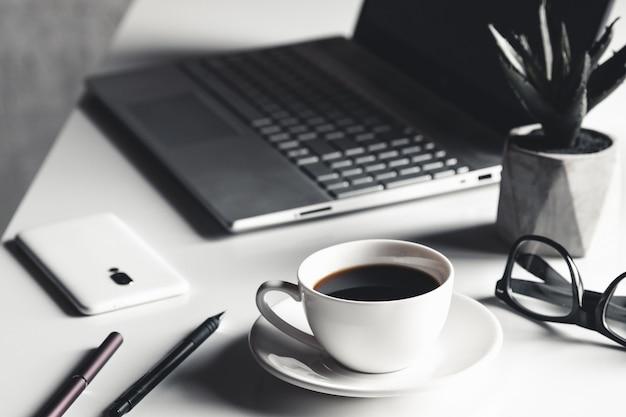 Zakenman met behulp van laptopcomputer en hand typen op laptop toetsenbord met notebook pen bril en kop warme koffie