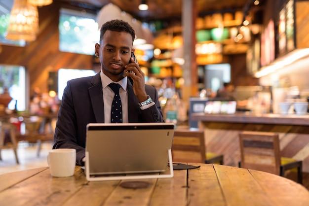 Zakenman met behulp van laptopcomputer en praten aan de telefoon bij coffeeshop