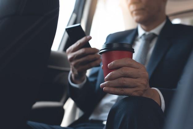 Zakenman met behulp van mobiele telefoon en koffie drinken in een auto