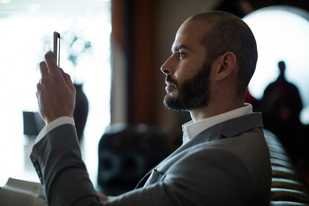 Zakenman met behulp van mobiele telefoon in wachtruimte