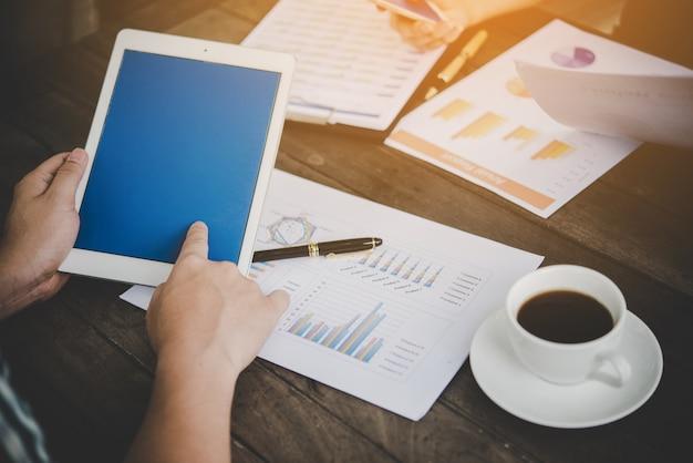 Zakenman met behulp van tablet naar analyse met business chart marketing rapport, werken op kantoor.