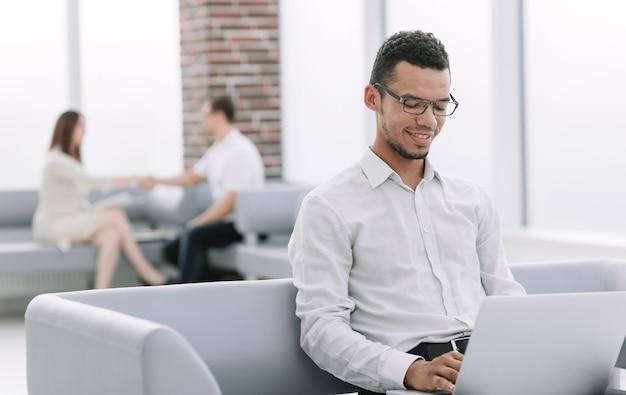 Zakenman met behulp van zijn laptop zittend in de lobby van het kantoor.