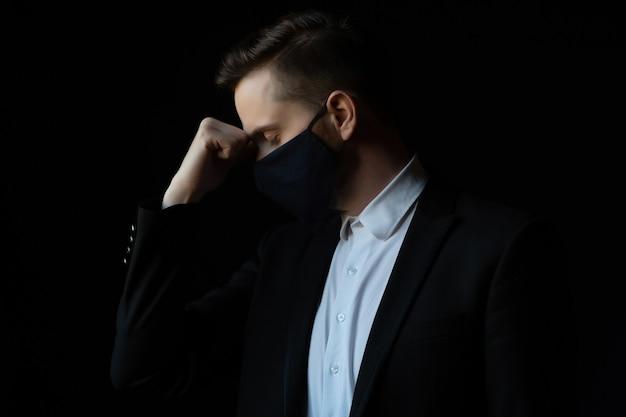Zakenman met beschermend masker in stress greep het hoofd met geïsoleerde hand