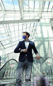Zakenman met beschermend masker op de luchthaven die de roltrap afgaat.