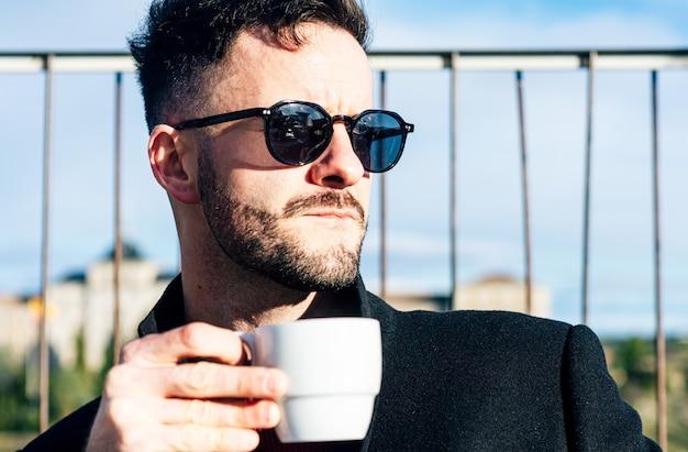 Zakenman met bijgesneden baard en zonnebril met een kopje koffie op het terras van een bar