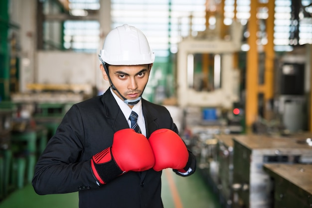Zakenman met bokshandschoenen in fabriek