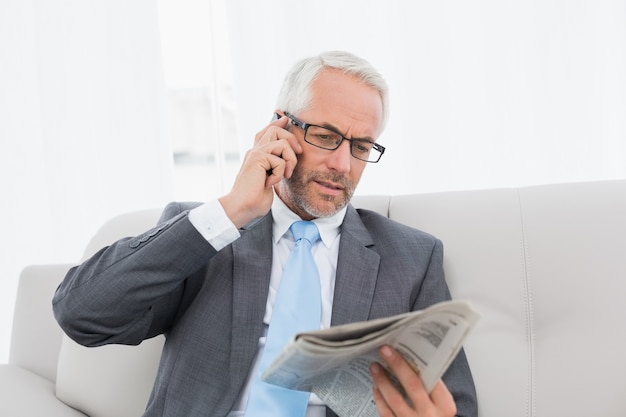 Zakenman met cellphone en krant thuis