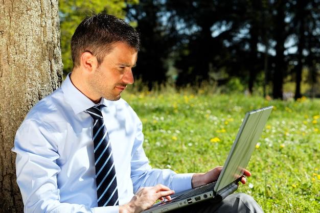 Zakenman met computer in een park in de zomer