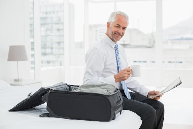 Zakenman met de koffiekop krant lezen door bagage