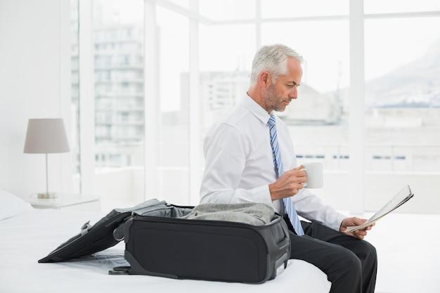 Zakenman met de krant van de koffiekop lezing door bagage bij hotelruimte