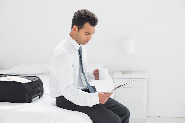 Zakenman met de krant van de koplezing bij hotelruimte