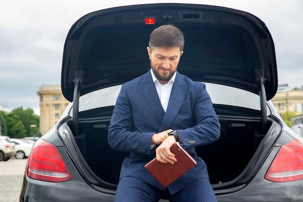 Zakenman met documenten zit in de buurt van een prestigieuze auto en kijkt op zijn horloge