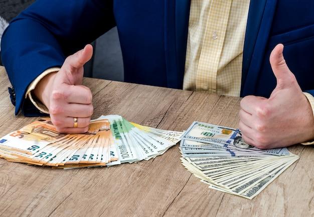 Zakenman met dollar en eurobankbiljetten beduimelt omhoog