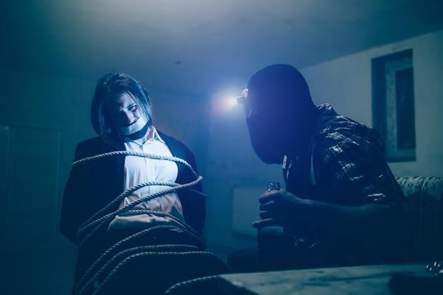 Zakenman met donker haar zit op een stoel. hij is eraan vastgebonden met touwen. kerel heeft zijn mond gesloten met plakband. hij kijkt naar zijn ontvoerder. man in masker heeft gloeilamp op zijn voorhoofd.