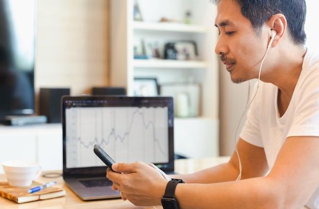 Zakenman met een bril die mobiele telefoon gebruikt terwijl hij thuis aan een laptop werkt