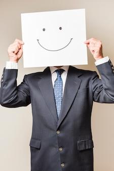 Zakenman met een glimlach op een document dat zijn gezicht behandelt