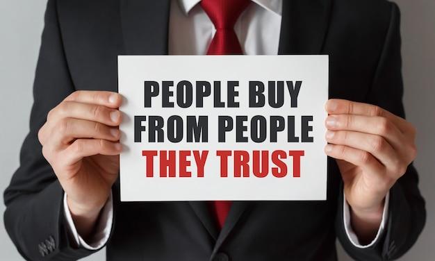 Zakenman met een kaart met tekst mensen kopen van mensen die ze vertrouwen