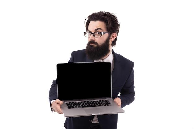Zakenman met een laptop, het optrekken van een wenkbrauw kijken naar de camera, geïsoleerd op een witte achtergrond