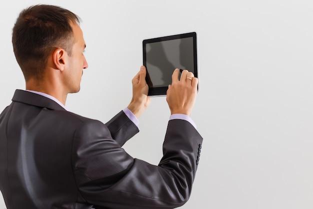 Zakenman met een leeg wit bord, uithangbord, met een leeg reclamebord tegen een witte achtergrond