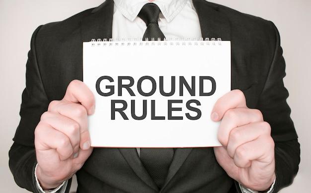 Zakenman met een notitieblok met tekst ground rules