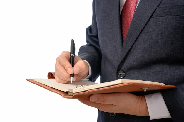 Zakenman met een notitieboekje in zijn hand en een pen om iets te schrijven.