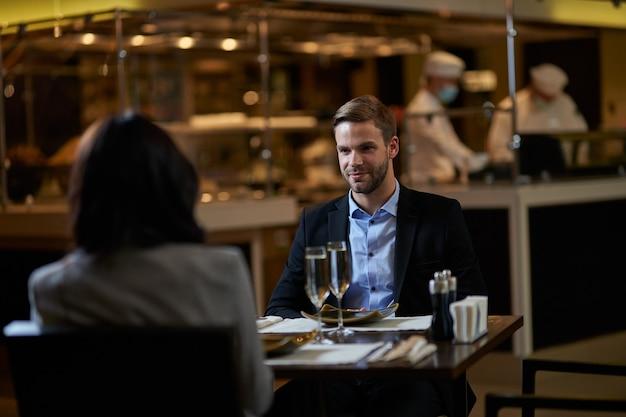 Zakenman met een officiële lunch met zijn vrouwelijke partner in restaurant met een paar volle wijnglazen ertussen