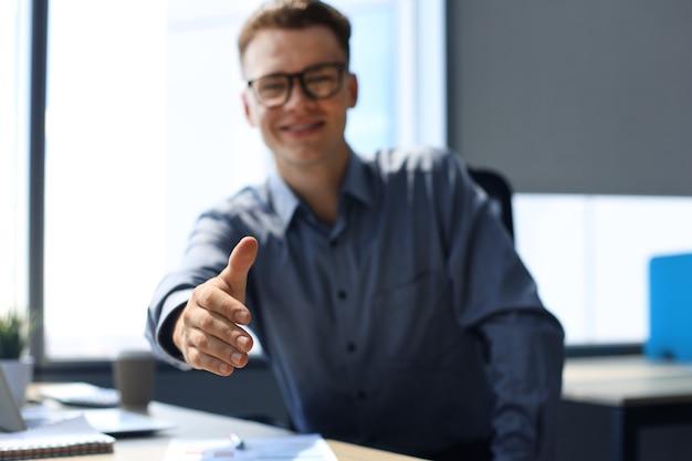 Zakenman met een open hand klaar om een deal op kantoor te sluiten.