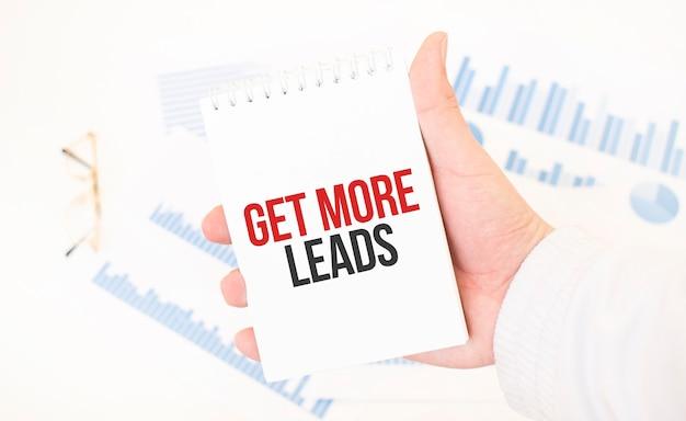 Zakenman met een witte blocnote met tekst get more leads