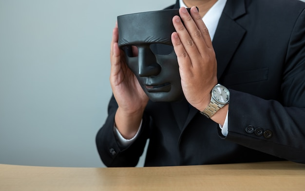 Zakenman met een zwart masker voor de onoprechtheid van samen zakendoen.
