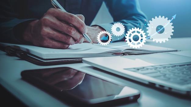 Zakenman met financiële rapporten een telefoon en laptop op een tafel met digitale versnellingen