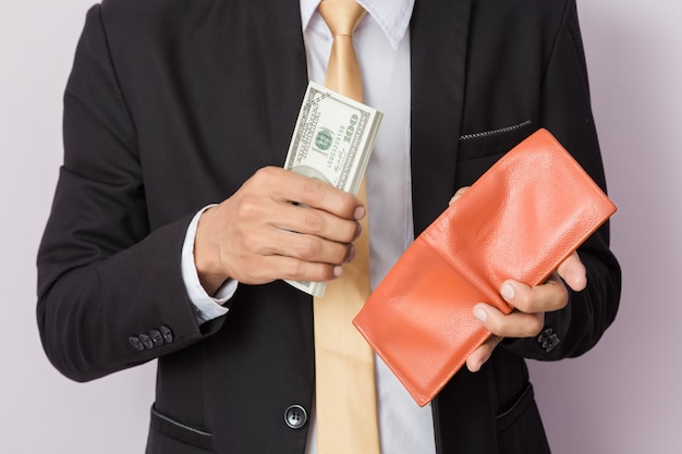 Zakenman met geld en oranje portefeuille in studio. bedrijfsconcept