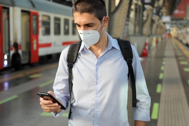 Zakenman met gezichtsmasker wachten trein op het station