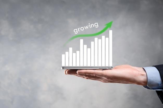 Zakenman met holografische grafieken en beursstatistieken winnen winst. concept van groeiplanning en bedrijfsstrategie. weergave van een goede economie formulier digitaal scherm.