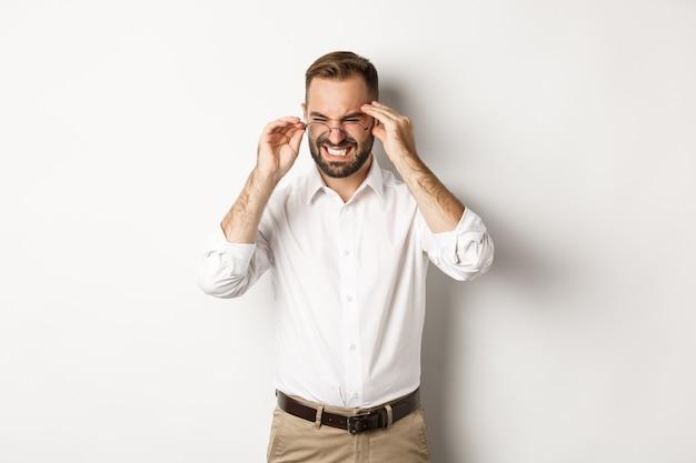 Zakenman met hoofdpijn, grimassen en hand in hand op het hoofd, staande op een witte achtergrond.
