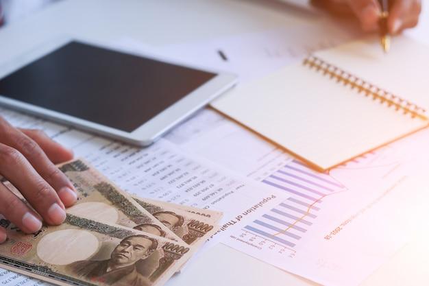 Zakenman met in hand geld, yen, investering, succes en voordelige bedrijfsconcepten.