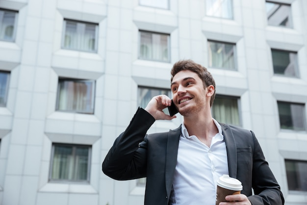 Zakenman met koffie praten over de telefoon