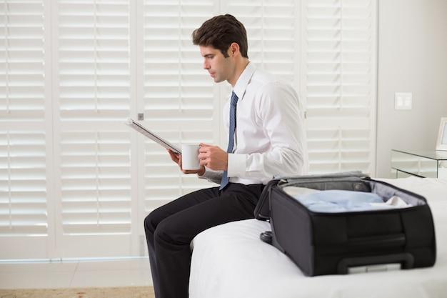 Zakenman met koffiekop en krant door bagage bij hotelruimte