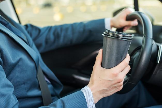 Zakenman met koffiekop in auto