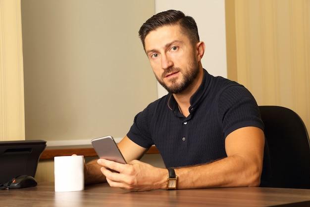 Zakenman met kop en mobiele telefoon in de hand aan de tafel zitten
