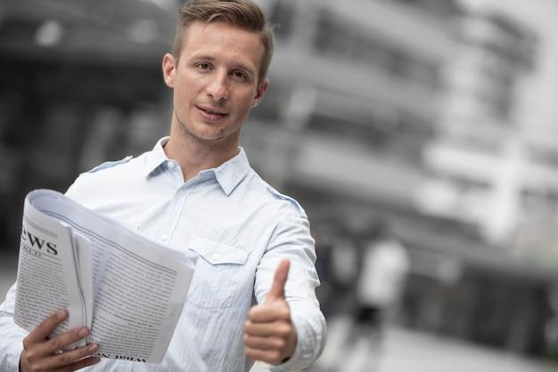 Zakenman met krant die duim voor goed nieuws opgeeft.