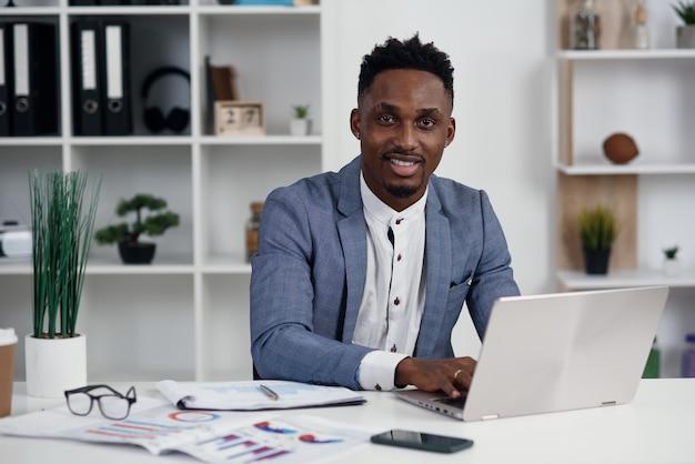 Zakenman met laptop. de jonge afrikaanse zakenman typt iets op laptop in zijn bureau.