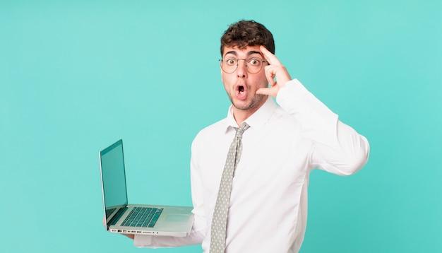 Zakenman met laptop die verrast, met open mond, geschokt kijkt en een nieuwe gedachte, idee of concept realiseert