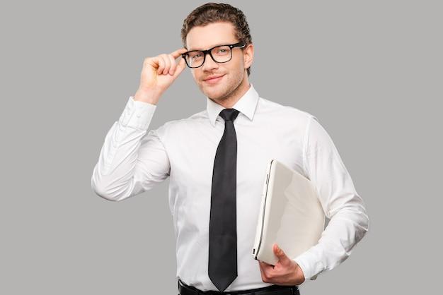 Zakenman met laptop. knappe jonge man in overhemd en stropdas die zijn bril aanpast en laptop vasthoudt terwijl hij tegen een grijze achtergrond staat Premium Foto