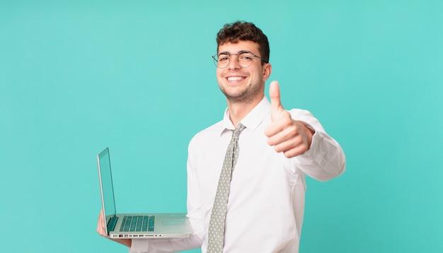 Zakenman met laptop voelt zich trots, zorgeloos, zelfverzekerd en gelukkig, positief glimlachend met duimen omhoog