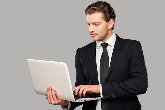 Zakenman met laptop. zelfverzekerde jonge man in formalwear die op laptop werkt terwijl hij tegen een grijze achtergrond staat