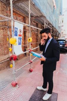 Zakenman met map praten over de telefoon
