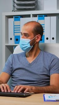 Zakenman met medische bescherming gezichtsmasker typen op computer in kantoorruimte. ondernemer in nieuwe normale persoonlijke werkplek zakelijk schrijven op pc-toetsenbord kijkend naar desktop