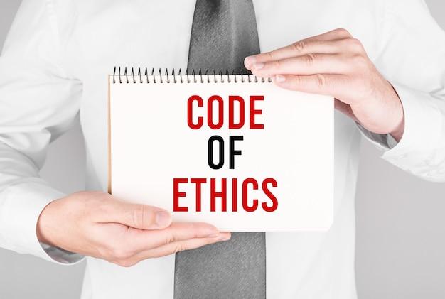 Zakenman met notitieboekje met tekst code of ethics