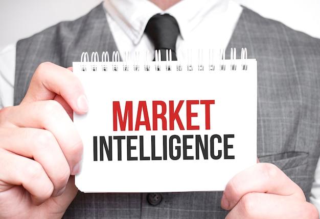 Zakenman met notitieboekje met tekst market intelligence