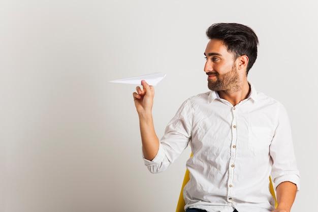 Zakenman met papieren vliegtuig op kantoor